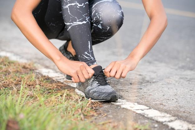 Corridore femminile di forma fisica di sport che si prepara per pareggiare all'aperto sul sentiero nel bosco. legame le scarpe.