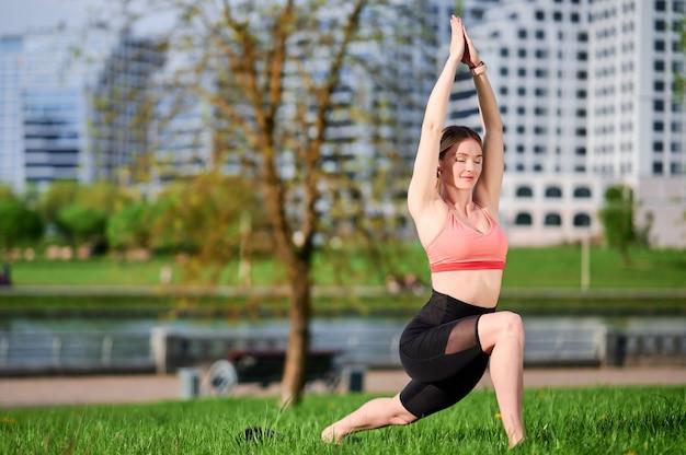 Donna in abiti sportivi che fa yoga in piedi nella posa del guerriero nel parco