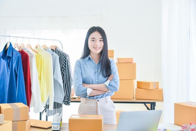 Proprietario di una piccola impresa di avvio femminile in piedi con il braccio incrociato e sorride