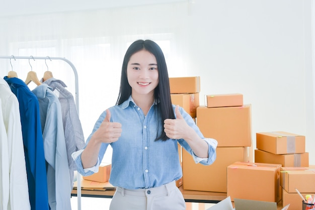 Proprietario di una piccola impresa di avvio femminile in piedi con un sorriso e che mostra i pollici in su