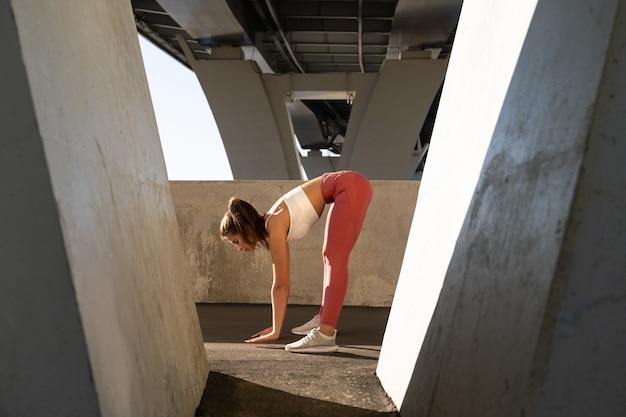 Gambe elastiche femminili e schiena all'aperto su sfondo urbano