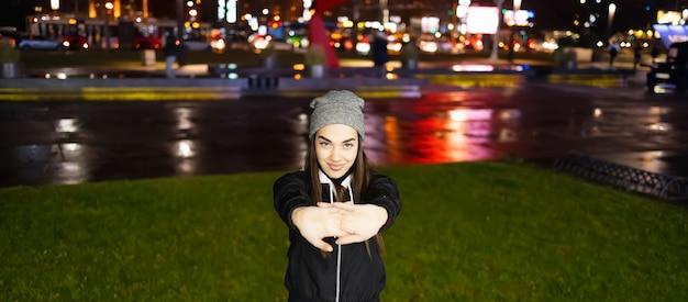 Donna che allunga le gambe prima del suo allenamento all'aperto in una bella notte in una grande città