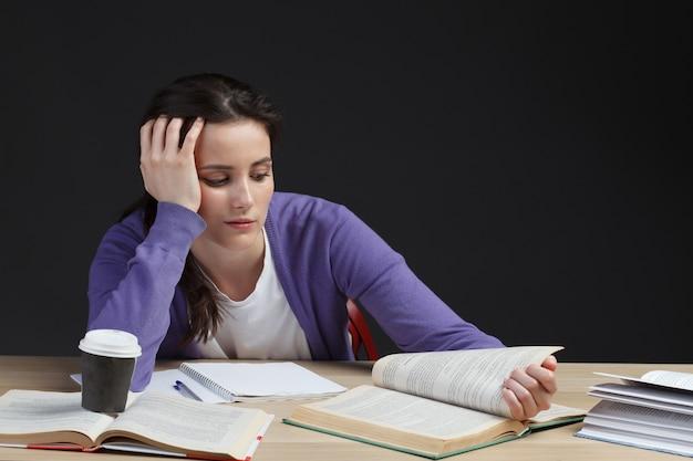 Studentessa noiosa per la lettura di libri di istruzione sullo scrittorio del college isolato