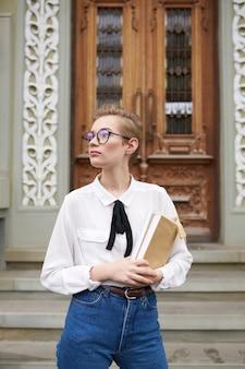 Studentessa in jeans e occhiali vicino alla porta sulla facoltà dell'istituto di istruzione della strada