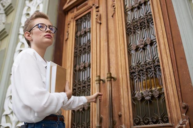 Studentessa vicino alla porta dell'edificio sull'istituto di istruzione esterna della strada