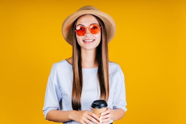 Studentessa in bicchieri rosa con un bicchiere di caffè in mano