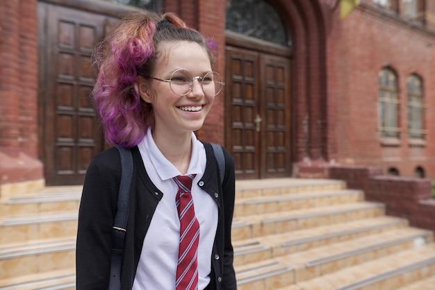 Adolescente studentessa in uniforme con zaino, sfondo della scuola di costruzione. ritorno a scuola, ritorno al college, istruzione, concetto di adolescenti