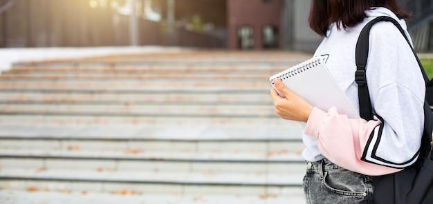 Una studentessa con uno zaino nero e un taccuino in mano si trova sui gradini di fronte all'università. l'istruzione superiore, l'inizio dell'anno scolastico, il ritorno a scuola. copyspace