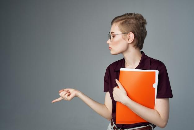 Studentessa con una cartella arancione in mano vista ritagliata