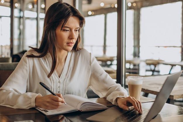 Studentessa che lavora al computer portatile e che prende appunti