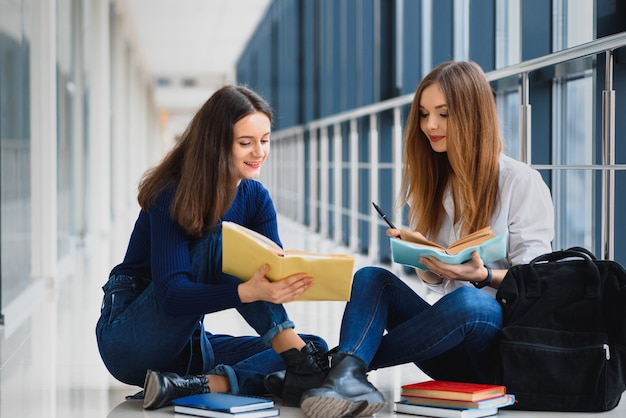 Studentesse sedute sul pavimento e leggere appunti prima dell'esame
