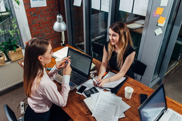 Studentesse che lavorano su compiti scolastici utilizzando computer portatili seduti alla scrivania in una sala studio.