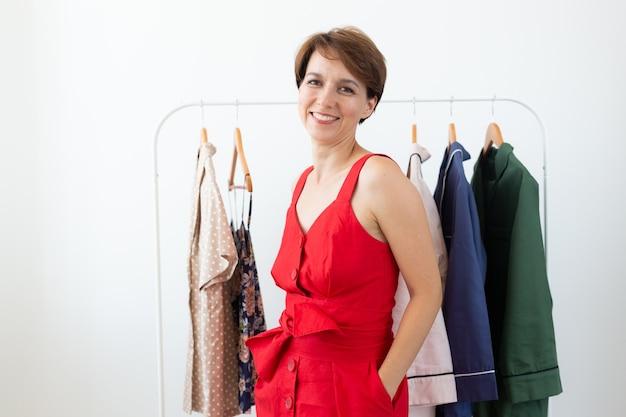 Stilista femminile vicino a cremagliera con grucce. shopping, designer di abbigliamento e concetto di consumismo.