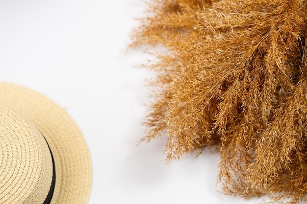 Cappello estivo femminile ed erba secca su sfondo bianco. vacanze estive, vacanze, viaggi, concetto di viaggio. vista dall'alto di accessori da spiaggia. spazio per il testo.