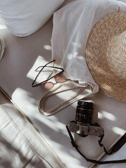 Occhiali da sole femminili, cappello di paglia, borsa shopper, macchina fotografica retrò su divano bianco con cuscini