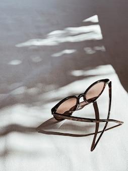 Occhiali da sole femminili su sfondo bianco con ombre di luce solare sfocate