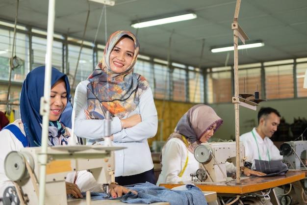 Supervisore femminile con il velo sorridente con le mani incrociate si erge a lato della sarta usando il...