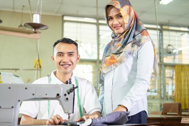 Il supervisore femminile sta accanto al dipendente che lavora con la macchina da cucire