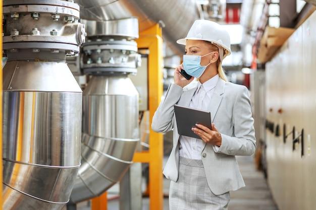 Supervisore femminile in tuta, con casco sulla testa, con maschera protettiva che tiene tablet e parla al telefono con un importante partner commerciale mentre si cammina nella centrale termica durante la pandemia della corona