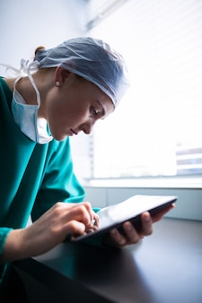 Chirurgo femminile che per mezzo della compressa digitale
