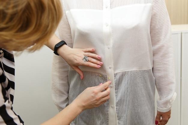 Sarto femminile che misura donna shouder per realizzare un abito su misura per una bella cliente nella sua sarta
