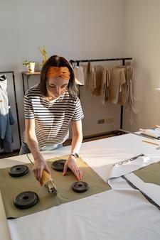 Il sarto femminile usa la macchina da taglio per i tessuti, il designer di vestiti per le ragazze o il sarto da donna lavora su una nuova collezione