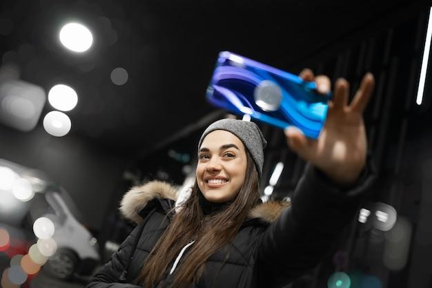 Femmina che cattura un selfie nelle luci della città