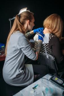Il tatuatore femminile in guanti sterili blu fa il tatuaggio dalla macchina, maestro in salone. processo di tatuaggio professionale in studio