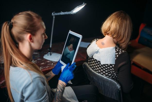 Il tatuatore femminile in guanti sterili blu fa il tiro del tatuaggio sulla parte posteriore del cliente. tatuaggio creativo in studio