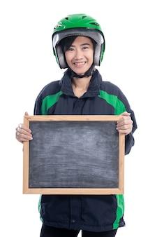 Motociclista di taxi femminile che indossa il casco tenendo lavagna vuota isolato su sfondo bianco
