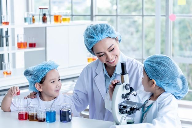 Insegnante femminile esperimenti con studenti bambini in laboratorio