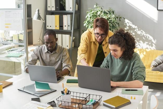Insegnante donna che spiega il lavoro online ai suoi studenti mentre lavorano al tavolo con i laptop