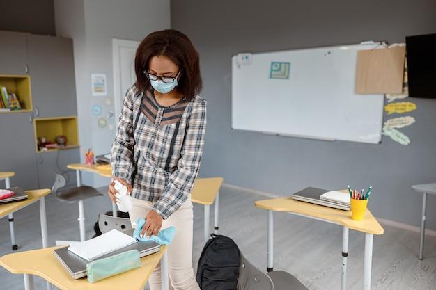 Insegnante femminile che tiene disinfettante e tovagliolo in classe