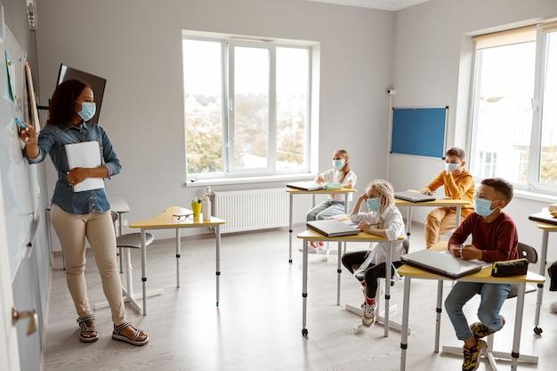 Insegnante femminile che tiene taccuino e pennarello in classe