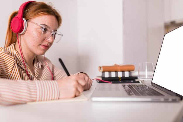 Insegnante femminile a casa in possesso di un corso online utilizzando laptop