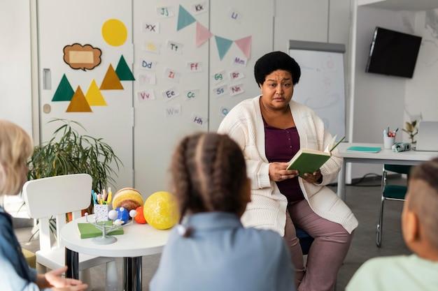 Insegnante femminile che legge per i suoi alunni