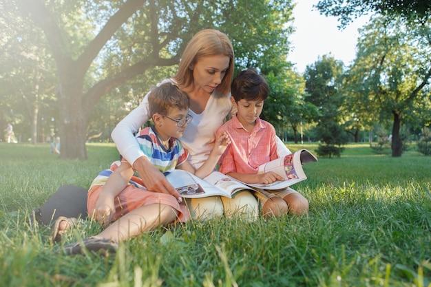 Insegnante femminile che legge con i suoi piccoli studenti, seduti sull'erba al parco pubblico
