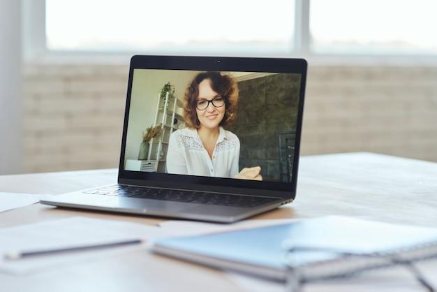 Insegnante donna che sorride alla telecamera durante la videochiamata mentre fa lezione online con gli scolari