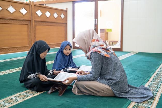 L'insegnante di sesso femminile insegna al suo studente a leggere il corano