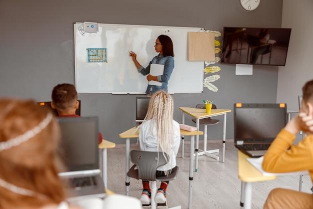 Insegnante femminile che insegna ai bambini in classe a scuola