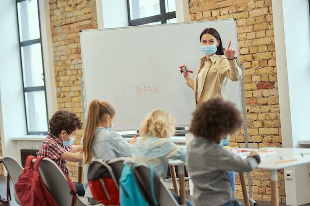 Insegnante donna che indossa una maschera protettiva durante la pandemia di coronavirus che scrive compiti matematici a bordo Foto Premium