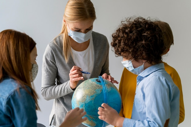 Insegnante femminile con mascherina medica che insegna geografia con il globo in classe