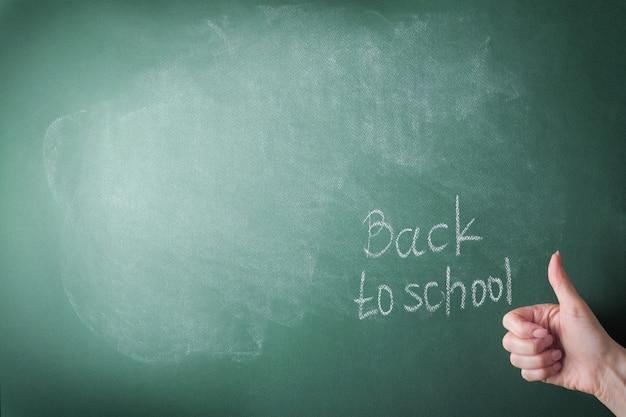 Insegnanti di sesso femminile la scrittura a mano sul consiglio scolastico torna a scuola gesso bianco. concetto di ritorno a scuola. mock up per il design. copia spazio. concetto di educazione.