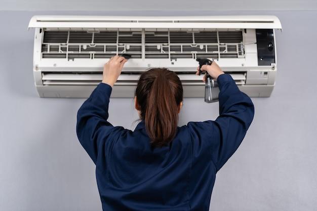 Servizio tecnico femminile che pulisce il condizionatore d'aria all'interno