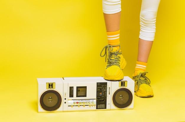 La gamba adolescente femminile in scarpe da ginnastica gialle si leva in piedi su un retro registratore. foto orizzontale