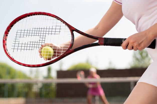 Giocatore di tennis femminile che tiene palla sopra la racchetta mentre va a lanciarla al compagno di giochi