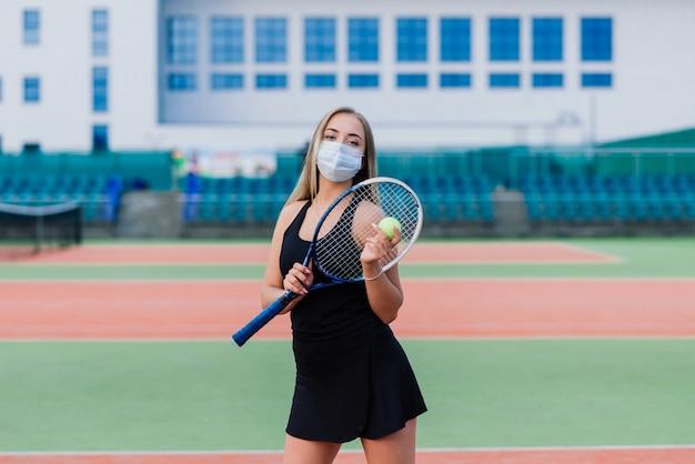 Giocatore di tennis femminile che gioca con la maschera protettiva