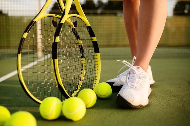 Giocatore di tennis femminile con la racchetta e molte palline sul campo all'aperto