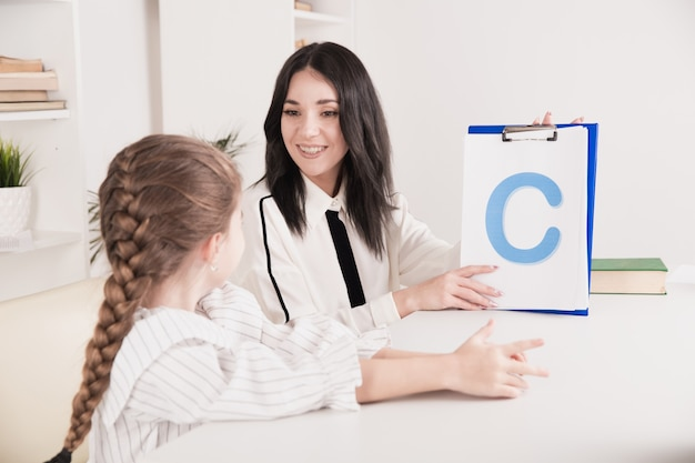 Terapista femminile che lavora con un bambino con problemi di pronuncia nell'armadio bianco.