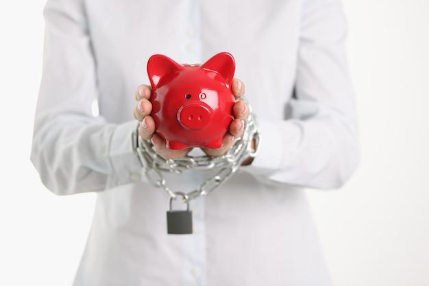 Le mani legate femminili con la catena tengono la dipendenza del porcellino salvadanaio di maiale rosso dal concetto di prestiti bancari
